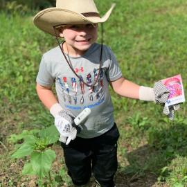 A young boy prepares to grow a Victory Garden with tools and seeds he received from Perry County NEP assistant, Reda Fugate.