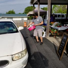 Safety first at the Metcalfe Count Farmers Market. A vendor brings his products to a drive-thru customer. Photo by Lynn Blankenship