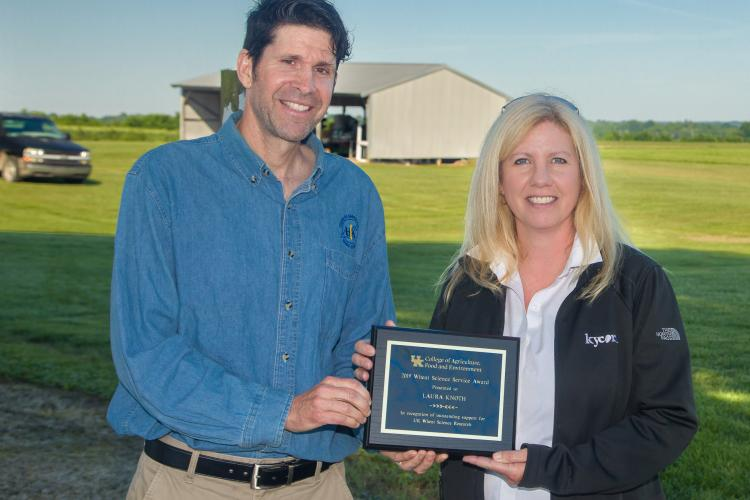 Bill Bruening of the UK Wheat Science Group presents Laura Knoth with the group's Service Award during the UK Wheat Field Day. Photo by Steve Patton, UK agricultural communications.