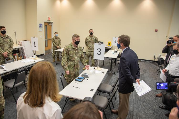 Gov. Andy Beshear learns how COVID-19 vaccines will be administered at the Henderson County Extension Expo building. Department of Defense soldiers from Fort Hood, Texas are assisting with the administration of vaccines at this location.