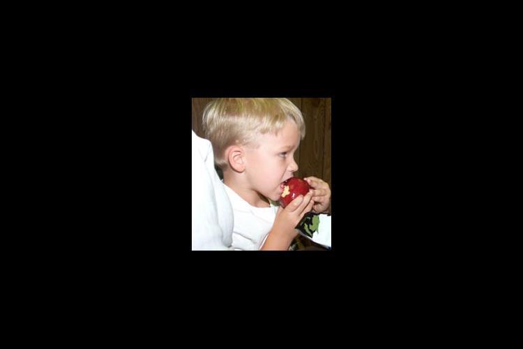 Five-year old Tyler Barrett enjoys a delicious apple as part of Breathitt County's summer feeding program.