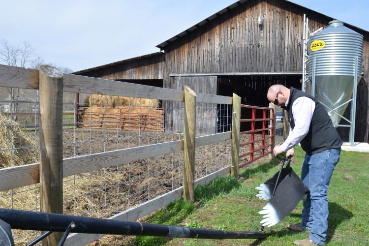 Johnson County farmer Tyler Ferguson hangs his black vulture effigy on an old basketball goal post.