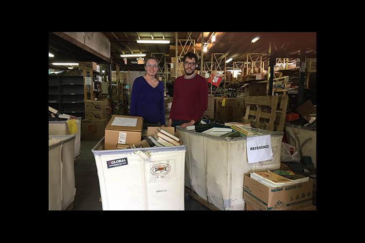 BAE's Carmen Agouridis and an IBP representative display donations from the 2017 Alpha Epsilon Book Drive