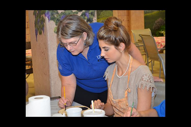 Brenda Cockerham, left, works with Katherine Dale on a piece of artwork at the Oil Springs Cultural Arts and Recreation Center.
