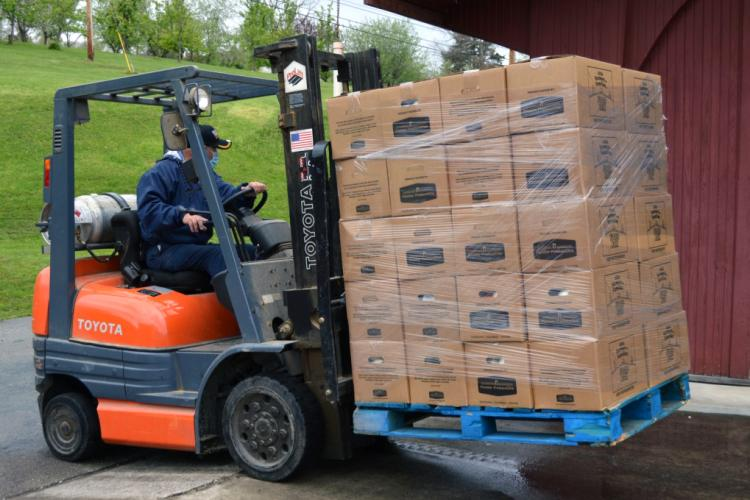 Forklift carrying a pallet of food boxes