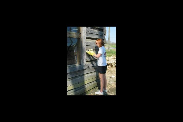 student cleaning cabin exterior