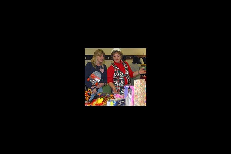 EFNEP Assistant Brenda Childers helps a client pick out gifts for her children at the Toy Store.