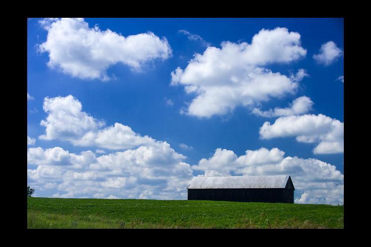 Clouds, blue sky, barn on a hill