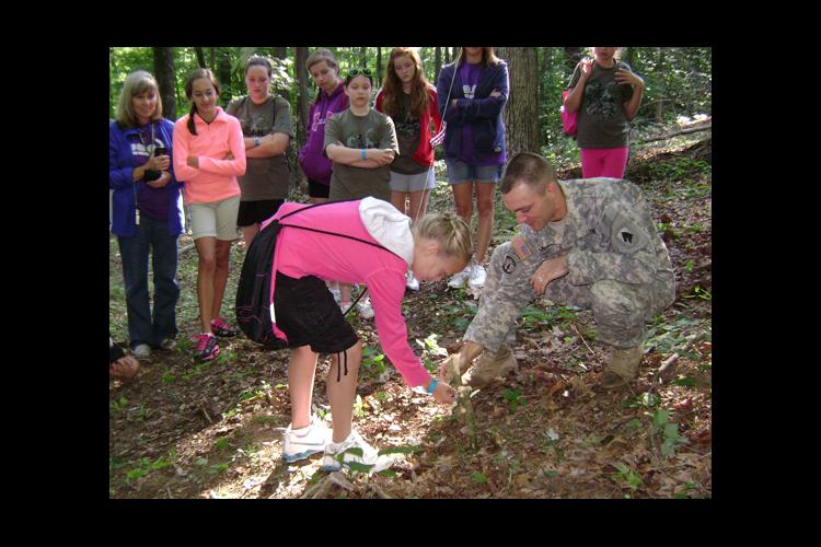 Staff Sgt. Joshua Meadors, right, assists a 4-H'er in building a trap during 4-H camp.
