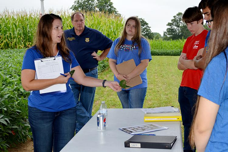 Kiersten Wise, UK extension plant pathologist, shows a team from Livingston Central an example of issues they might find in the adjoining soybean plot during the 2019 UK High School Crop Scouting Competition.