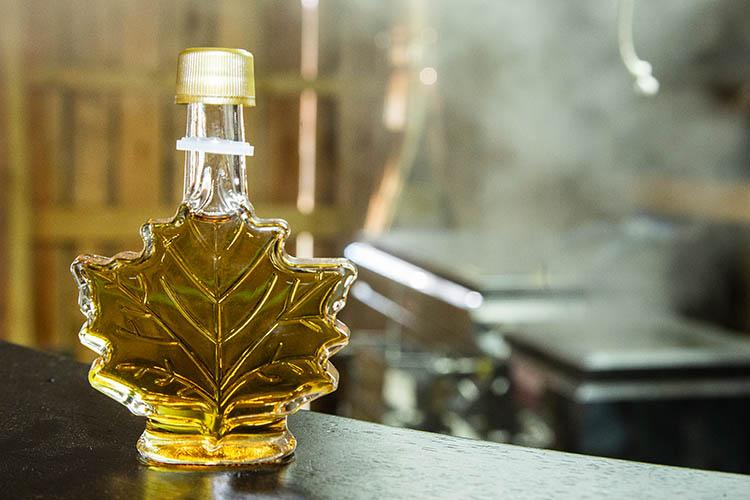 Filled maple syrup bottle in foreground, boil down of sap in background