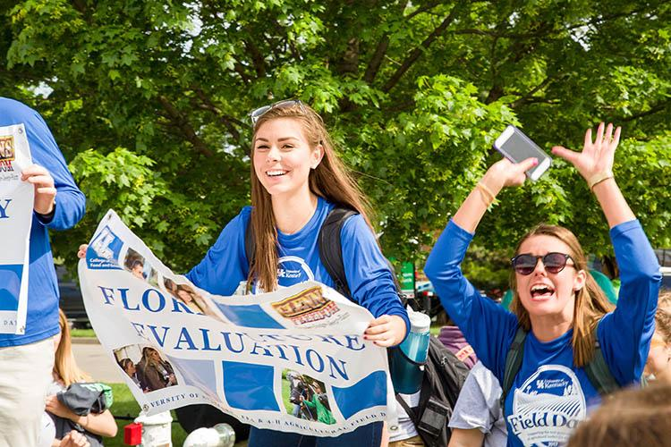 UK CAFE students hold signs aloft to guide 4-H and FFA members.