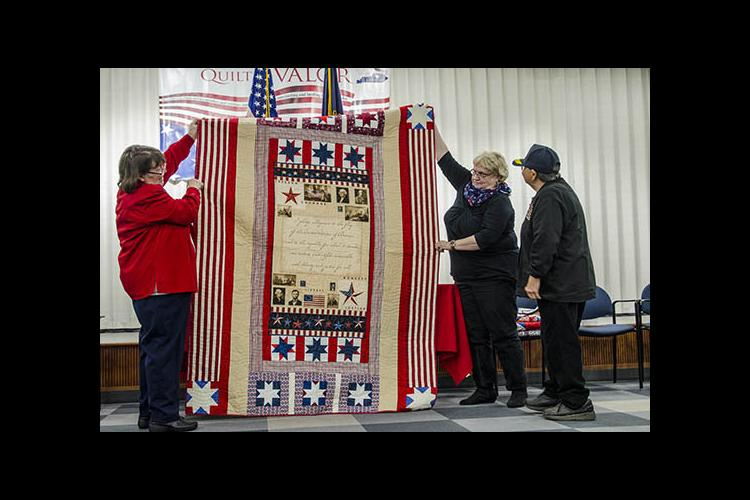 A quilt is awarded to a veteran during a Quilts of Valor ceremony at the Fayette County Extension office.