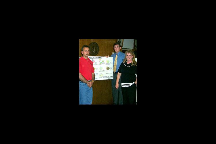 The 2000 Heritage Plan suggests land use guidelines using state-of-the-art graphics. Pictured are community leader Charles Ray Pennington (left), UK student Jeff Townsend (center), and Elliott County Extension Agent Gwenda Adkins.