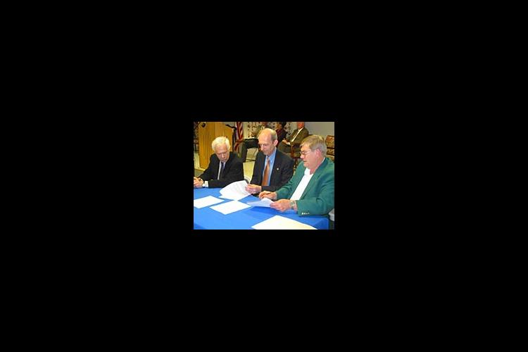 Robert Shay, Larry Turner and Larry Dotson sign a memorandum of understanding to work together in promoting fine arts in Kentucky.