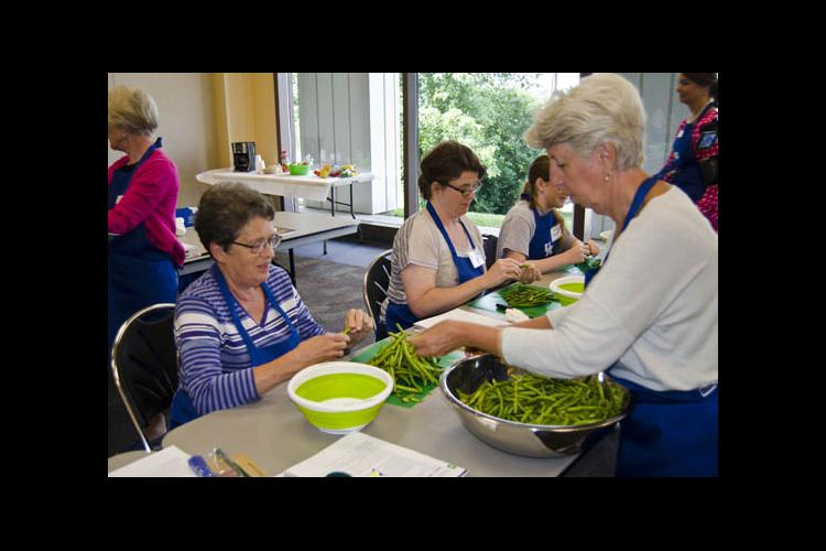 Cheryl Case, right, helps a food preservation workshop particpant break beans.
