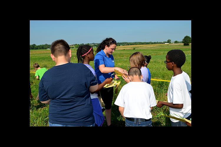Sydney Beidleman, center, UK forage intern, helps Millcreek Elementary students identify weeds.