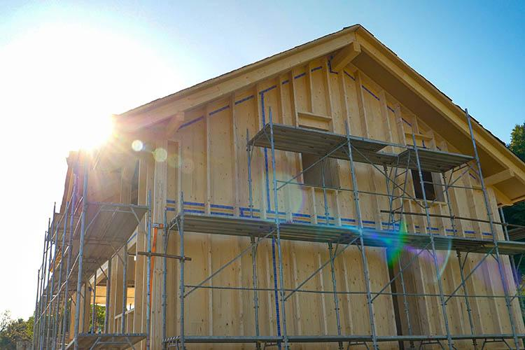 A lens flare over a cross-laminated timber house under construction