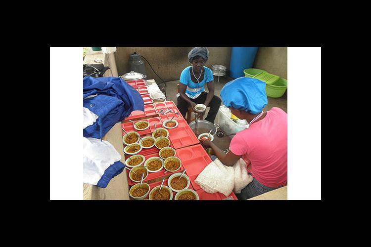 Female cooks serve food at the Kentucky Academy, a kindergarten in Adjeikrom, Ghana.