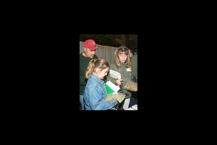 The Kramer family of Own County examines different types of goat rations at the recent Goat Day at Kentucky State University's Research Farm.