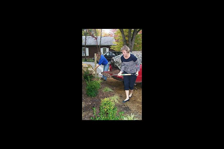 Elizabeth Rhoads, foreground, a member of the Hopkins County Horticulture Extension Council and Amy Fulcher, Hopkins County Extension agent for horticulture put mulch around newly planted landscaping at a home built by Habitat for Humanity in Madisonville