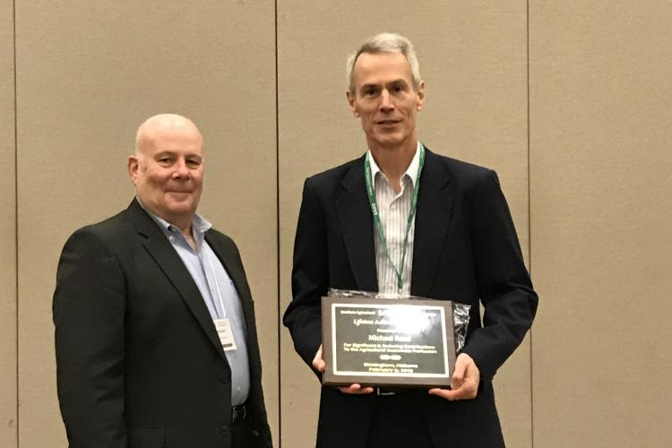 UK's Michael Reed, right, receives an Lifetime Achievement Award from Jeff Jordan, left, treasurer of the Southern Agricultural Economics Association. Photo by Barry Barnett, UK professor and chair of the Department of Agricultural Economics.