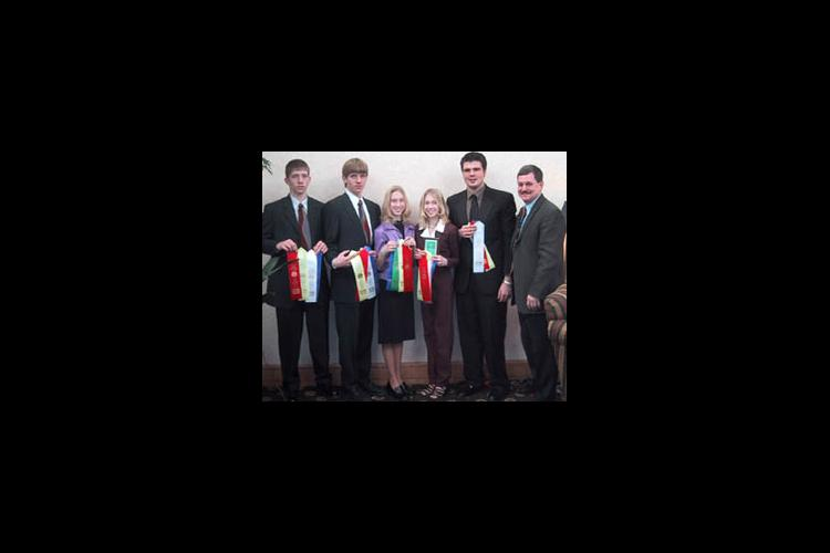 The 2002 Meat Judging team display their ribbons with coach Benjy Mikel (far right).