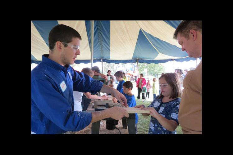 A UK Forestry student helps a family route a cutting board at the 2013 Kentucky Wood Expo.