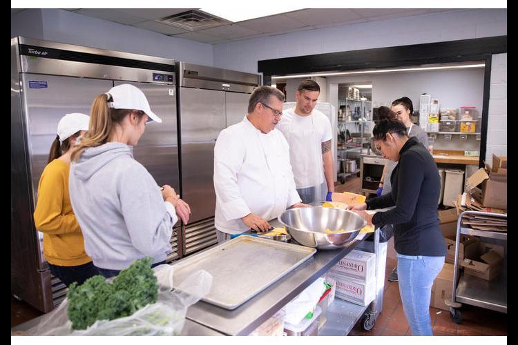 Chef Bob Perry instructs students how to slice a banana squash. Mark Cornelison   UK Photo.