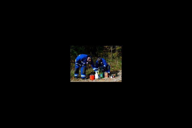 Members of the Pennyrile Narcotics Task Force clean up the remnants of an illegal methamphetamine lab.