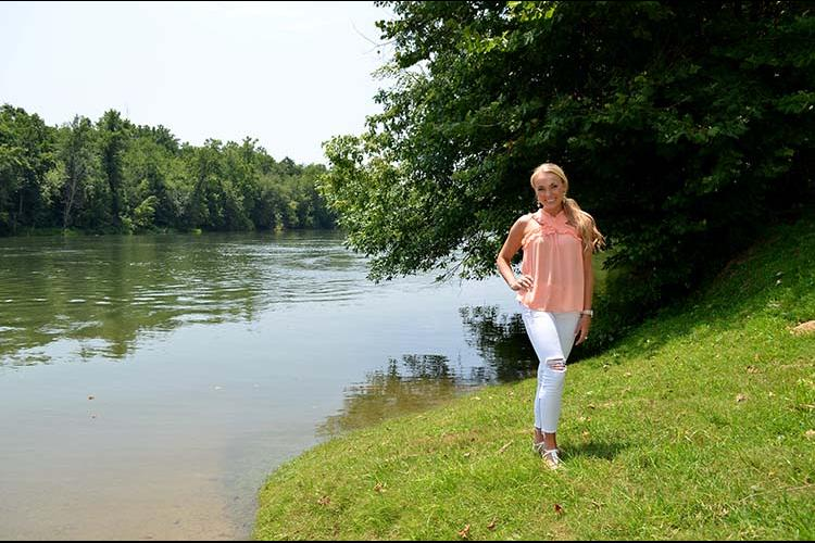 Molly Morgan stands next to the Cumberland River.