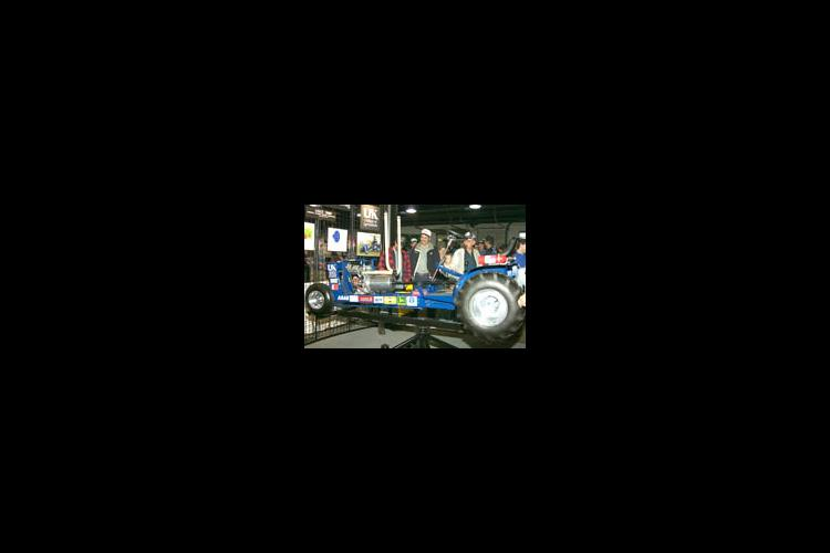 NFMS visitors look at a quarter-scale pulling tractor designed and fabricated by UK Agricultural Engineering students.