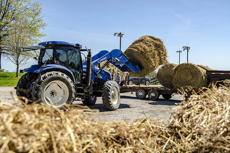 Volunteers stack bales of hay at the Owen County Fairgrounds for distribution to Nebraska farmers suffering from flooding.