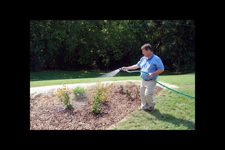 Rick Durham, UK consumer horticulture specialist waters a newly installed rain garden.