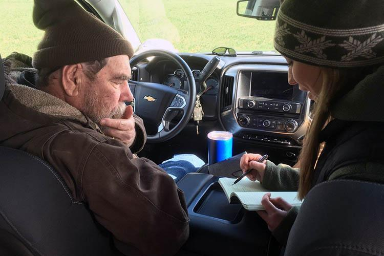 Richard Preston and Hanna Poffenbarger go over data in the car.