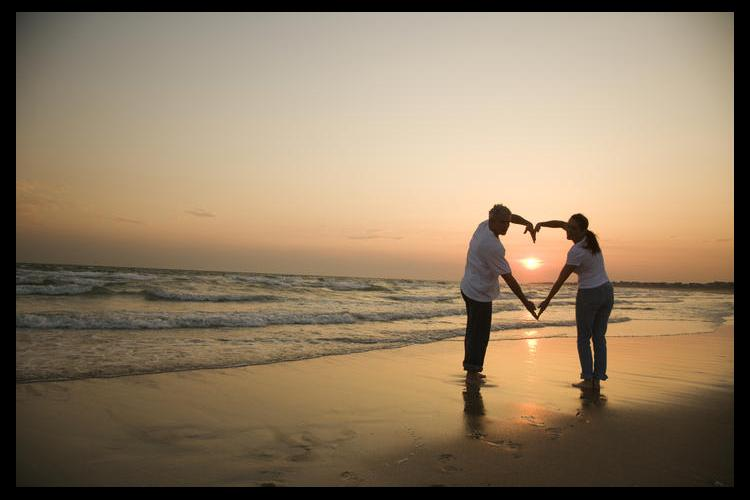 Sunset beach scene of couple making heart shape with arms