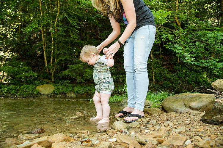 Baby dips its feet into a mountain stream in UK's Robinson Forest.