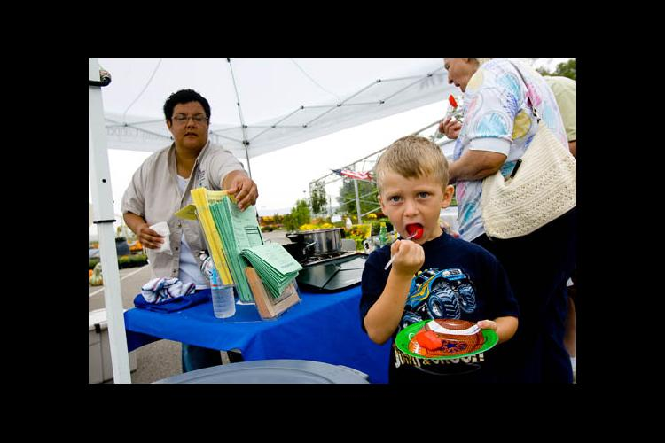 Aaron Begley, 4, tries some cinnamon apples at the Cooperative Extension booth at the Boone County Farmers Market.