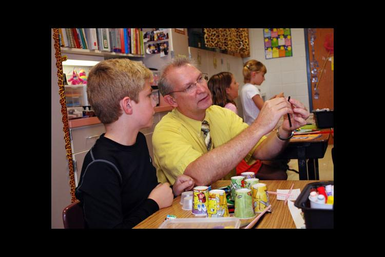 Southside Elementary teacher Tom Sheldon works with fifth-grader Preston Woods on the Eco-Bot Challenge.