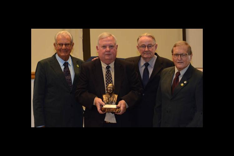 Bill Phillips, second from left, is presented with a bust of his father from Manoel Pereira, Franke Dijkstra and Herbert Bartz.
