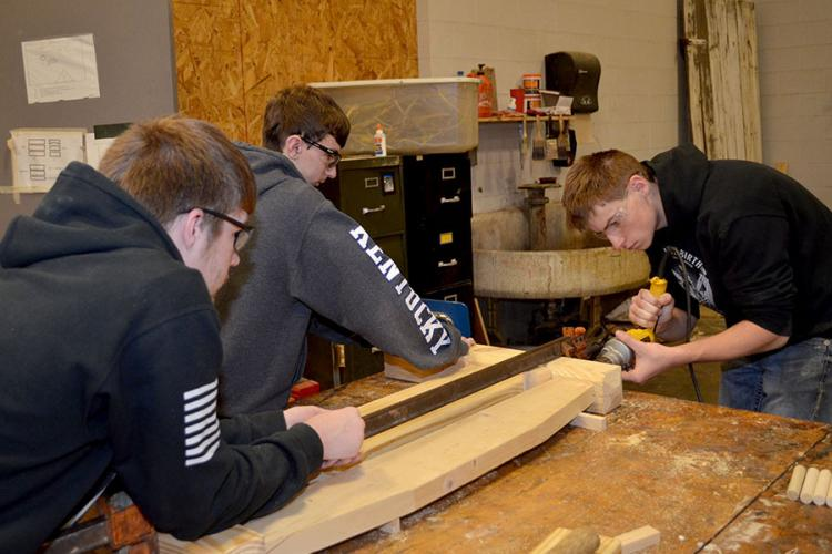 Wayne Johnson, a junior at Franklin-Simpson High School, drills holes in a headboard for dowel rods while Wyatt Shields, a junior, center, and Brandon Boyer,  a senior, left, secure the headboard. Photo by Katie Pratt, UK agricultural communications.