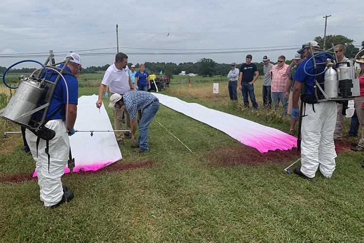 UK weed scientist Travis Legleiter, center, uses pink dye to demonstrate how nozzle size and boom height affect herbicide drift during the 2019 Spray Clinic. Photo by Lori Rogers, UK KATS coordinator.