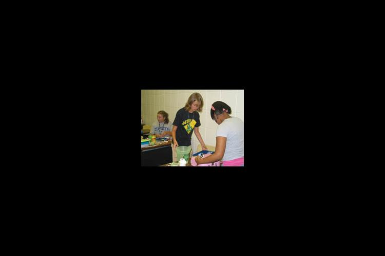 """Emma Huff (left), Jorden Patterson (middle) and Madison Cannon (right) put the finishing touches on their products for the """"Entrepreneurship for Teens"""" class during the 2006 4-H Teen Conference."""