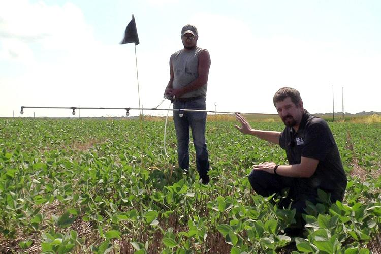 UK weed scientist Travis Legleiter, foreground, explains how boom height affects herbicide drift. Shawn Wood, UK senior lab technician, holds the spray boom. Photo provided.