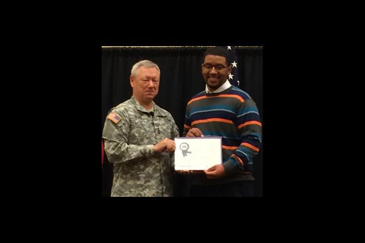 Gen. Frank Grass presents Tyrone Atkinson with the Youth Development Volunteer Award.