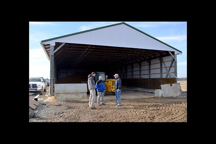 UK's Brad Hagan, left,  and Sam McNeill talk with Dan Hendrickson outside of his temporary grain storage structure.