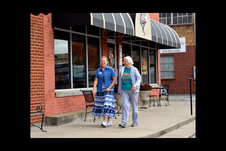 Missy Curry, left, and Suzanne Taylor walk on Greensburg's Merchant Mile.