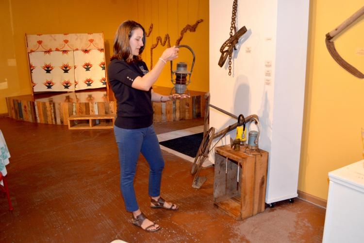 Cortney Moses shows on railroad lanterns that are on display in the ARTifacts exhibit.