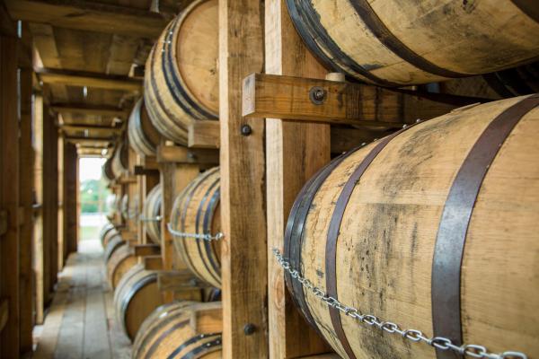 Bourbon barrels sitting in a rickhouse.