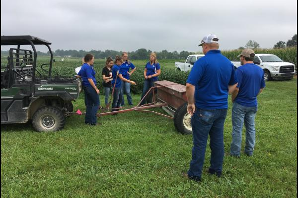 Grain and Forage Center of Excellence 2019 intern Hannah York, center, shows other interns how to calibrate a fertilzer spreader at the UK research farm in Princeton. Photo by Carrie Knott, UK grain crops specialist.